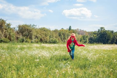 Little kid in red superhero costume running in meadow on summer day stock vector