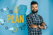 Photo bearded smiling businessman posing with crossed arms, on blue with plan icons