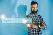 Fotografie bearded smiling seo developer posing with crossed arms, on blue with website search bar