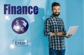 Fotografie usmívající se podnikatel v kostkované košili přes notebook, na modré s ikonami financí
