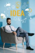 Photo smiling businessman sitting in grey armchair, on blue with idea icons