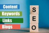 Photo SEO word made from wooden blocks on blue background with Content, Keywords, Links, Blogs signs