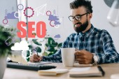 Photo successful seo manager with cup of coffee and computer writing notes at workplace with SEO icons