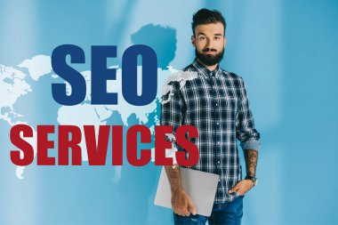 Bearded developer in checkered shirt holding laptop, on blue with world map and SEO services stock vector