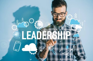 smiling businessman in checkered shirt pointing at leadership icons