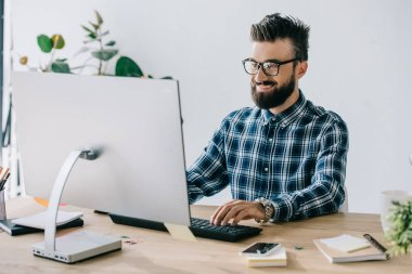 successful smiling young seo using computer at workplace