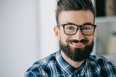 close-up portrait of bearded smiling man in eyeglasses looking at camera