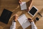 Fotografie pohled shora podnikatelé práce a psaní na dřevěný stůl s kávou a digitální tabletu