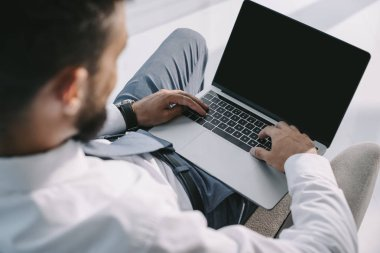 cropped view of businessman typing on laptop with copy space