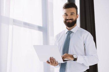 Bearded smiling businessman using laptop near window in office stock vector