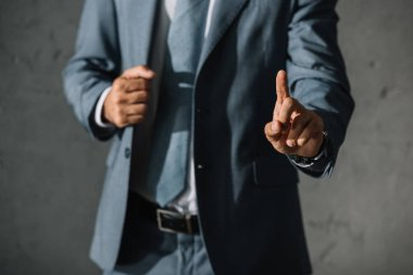 cropped view of businessman in formal wear pointing up