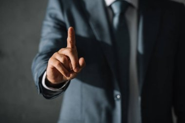 cropped view of businessman in suit pointing up with finger