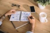 Oříznout záběr člověka psaní podnikatelského plánu v poznámkovém bloku na pracovišti