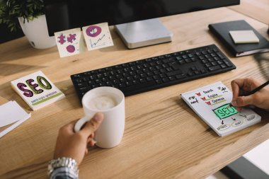 Cropped shot of seo manager writing notes with cup of coffee and computer at workplace stock vector