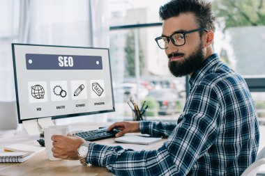 Young successful seo manager sitting at workplace with computer and looking at camera stock vector