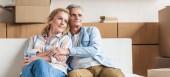 Coppie anziane felici che si abbracciano e distoglie lo sguardo mentre seduti insieme sul divano nella nuova casa