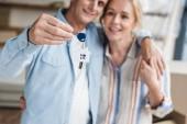 Detailní pohled šťastný staršího páru držícího klíče z nových nom během přemístění