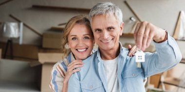 happy senior couple holding keys from new apartment and smiling at camera