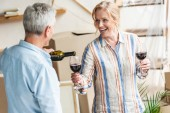 Photo senior man pouring wine to happy wife while relocating in new house