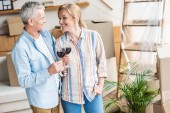 Photo happy senior couple holding glasses of wine and smiling each other during relocation