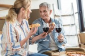 Photo happy elderly couple eating pizza and drinking wine in new house