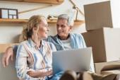glückliches Senioren-Paar benutzt Laptop und lächelt sich beim Umzug an