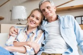 happy senior couple embracing and smiling at camera in new house