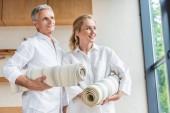 Fotografie gerne älteres paar hält Yoga-Matten und Wegsehen
