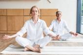 Fotografie älteres Ehepaar sitzt im Lotussitz und meditieren gemeinsam auf Yoga-Matten