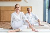 Fotografie gerne älteres paar Yoga zu praktizieren und lächelt in die Kamera