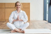 Fotografie happy mature woman sitting in lotus position with namaste gesture and smiling at camera
