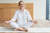 Fotografie happy mature woman sitting in lotus position and smiling at camera