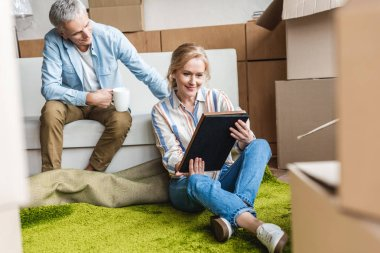 smiling senior couple looking at photo album while sitting between cardboard boxes in new house