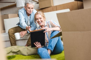 happy senior couple looking at photo album while sitting together in new house