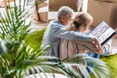 high angle view of senior couple looking at photo album while moving home