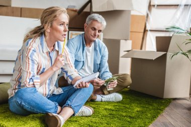 senior couple sitting on carpet and counting money during relocation