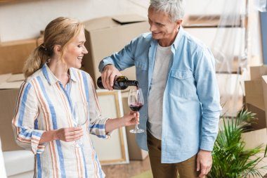 happy senior man pouring wine to wife while celebrating relocation