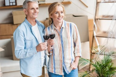 happy senior couple holding glasses of wine and looking away in new house