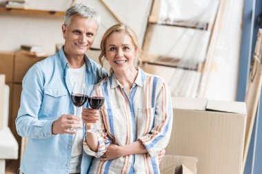 happy elderly couple holding glasses of wine and smiling at camera in new apartment