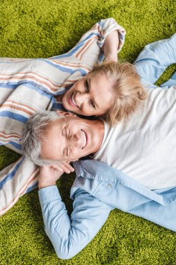 top view of happy senior couple lying together on green carpet