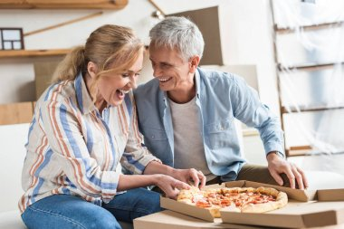 happy senior couple eating pizza and laughing in new house