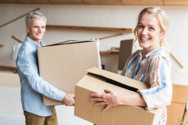 happy senior couple holding cardboard boxes and smiling at camera during relocation