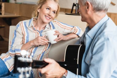 elderly woman holding cup and looking at senior husband playing guitar in new home