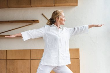 sporty mature woman performing warrior pose while practicing yoga