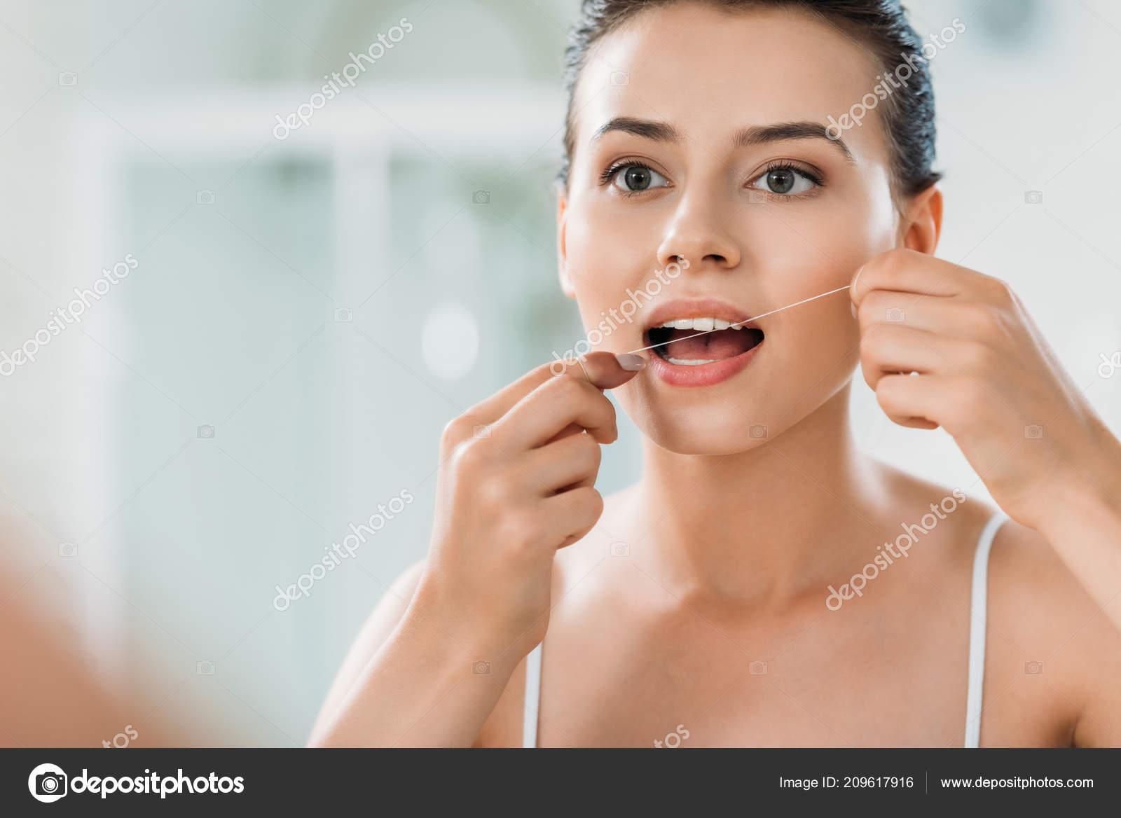 In Bathroom | Beautiful Young Woman Using Dental Floss Bathroom Fotos De Stock