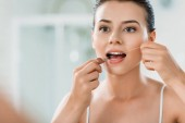 Fotografie beautiful young woman using dental floss in bathroom