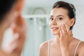 mosolygó fiatal nő, arc krém, és nézte a fürdőszobában tükör alkalmazása szelektív összpontosít