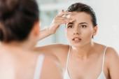 atraktivní mladá žena dotýká čela a při pohledu na zrcadlo v koupelně