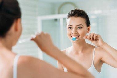 beautiful smiling girl brushing teeth at mirror in bathroom