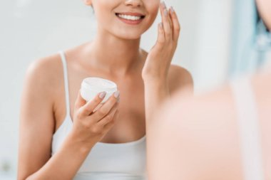 cropped shot of smiling girl holding container and applying face cream at mirror in bathroom